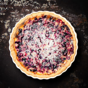 Homemade wild berry pie with sour cream, top view, toned