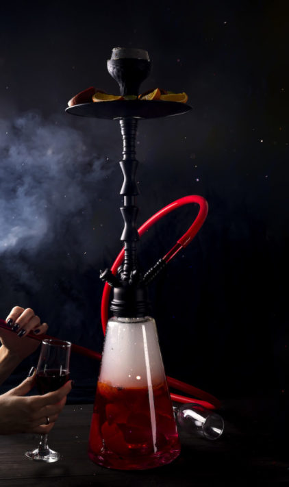 A girl with a glass of red wine smokes a fruit hookah